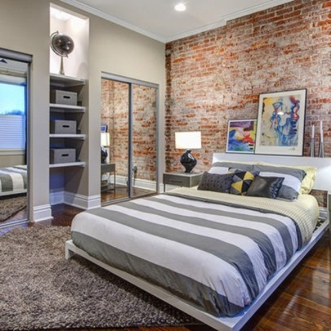 a traditional bedroom is spruced up with a red brick statement wall and rich stained wood floors