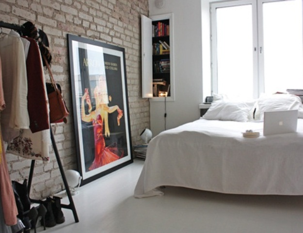 a Nordic bedroom with a brick wall, a white floor and an open closet features raw and simple aesthetics