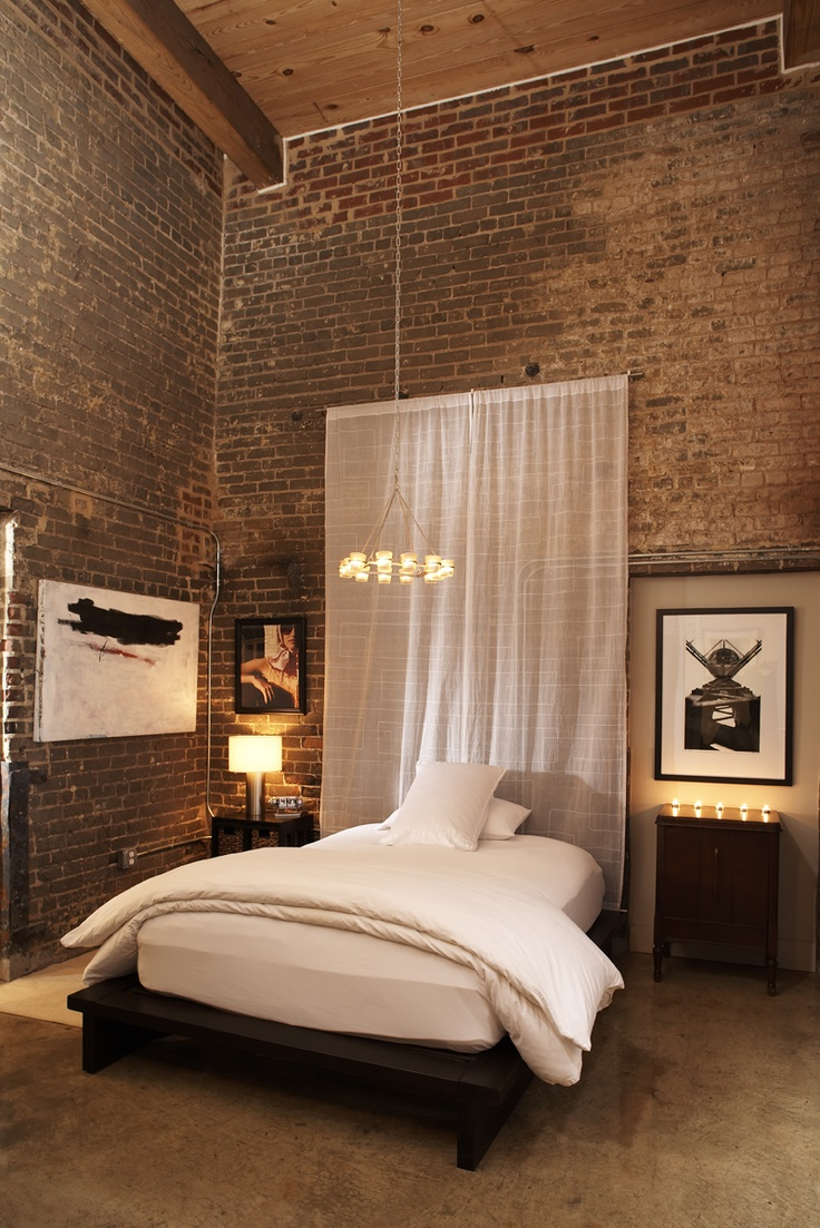 exposed brick double height walls are softened with an airy curtain, chic lamps and a stylish bed
