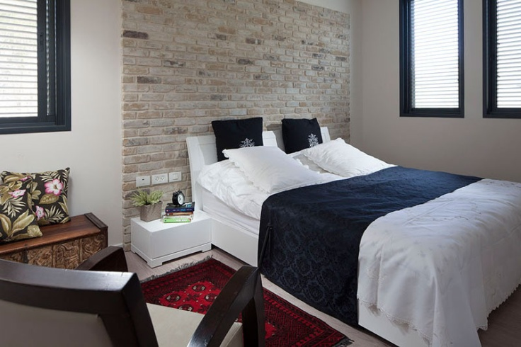 a small and chic bedroom with a fake brick wall done with panels that adds texture and a chic modern touch