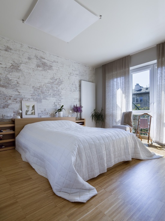a contemporary bedroom with a whitewashed and shabby brick wall that adds a raw feel to the space
