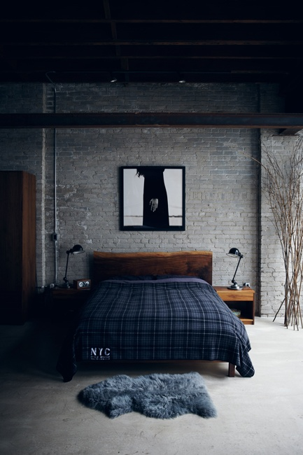 a moody masculine bedroom with a grey brick statement wall and chic mid-century modern furniture
