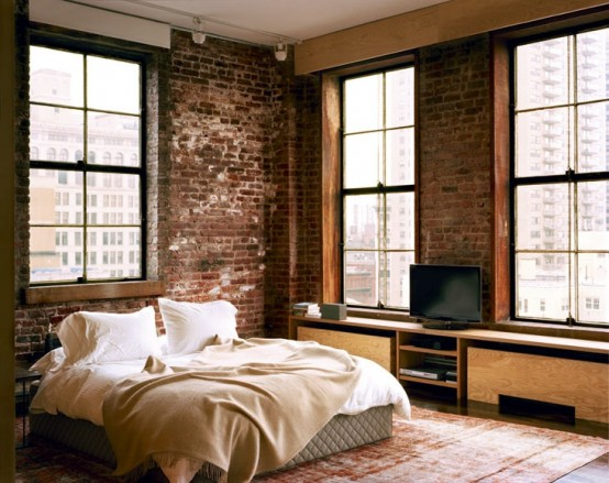 a stylish bedroom with brick walls, plywood furniture and boho rugs plus an upholstered bed