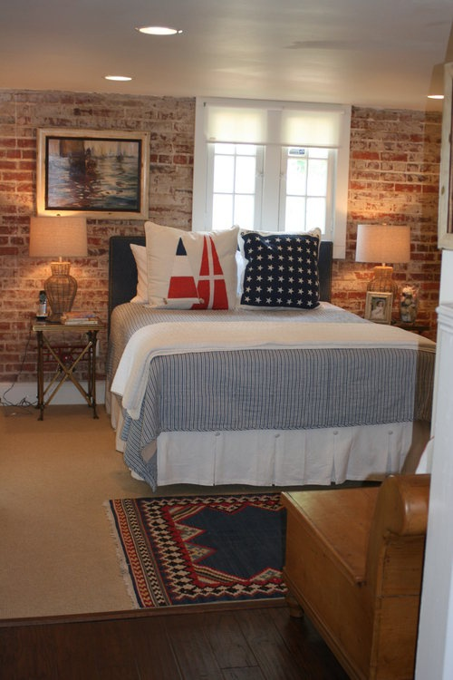 a mid-century modern bedroom with a brick wall, printed textiles and wicker and burlap lamps