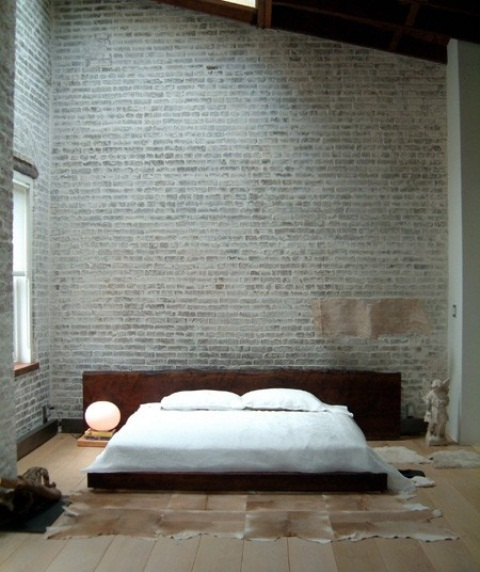 a sleek contemporary bedroom with grey brick walls, a livign edge wooden bed and faux animal skins on the floor