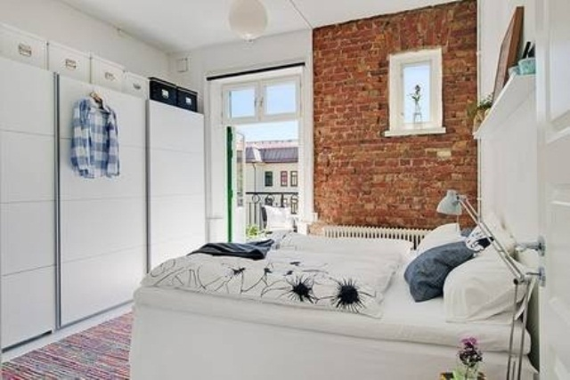 a white Scandinavian bedroom is refreshed with a single exposed brick wall that adds color and texture