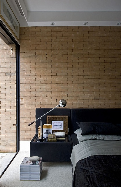 a contemporary bedroom with a faux brick wall of a sandy shade and a velvet upholstered black bed
