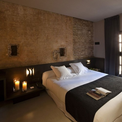 a stone and brick wall brings more interest to the space and a black upholstered bed contrasts it