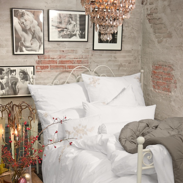 partly painted and partly no brick wall, a forged bed and a crystal chandelier create a gorgeous space