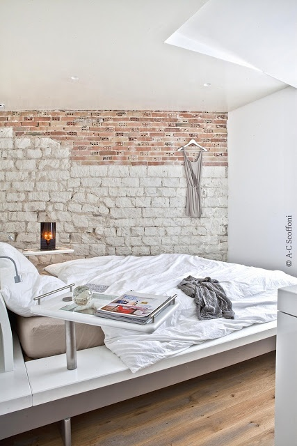 an ultra-modern bedroom with a chic bed is made bolder and catchier with a faux stone and brick wall created with a mural