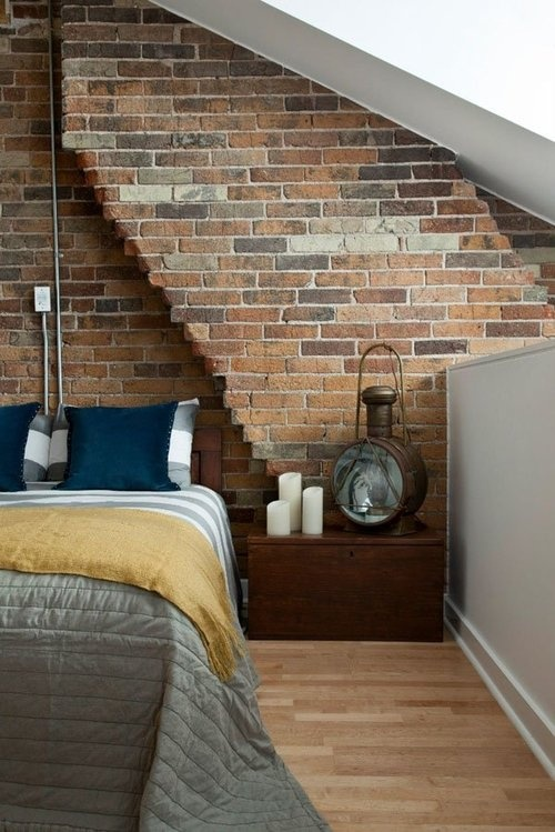 a moody bedroom with a dark brick wall going with a sculptural line, vintage furniture and accessories show off the style of the owner