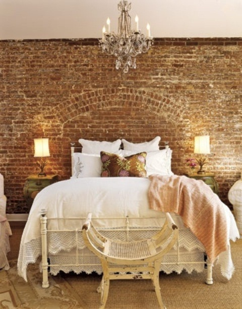 a girlish vintage bedroom with a sandy brick wall, a metal bed and shabby chic and vintage items