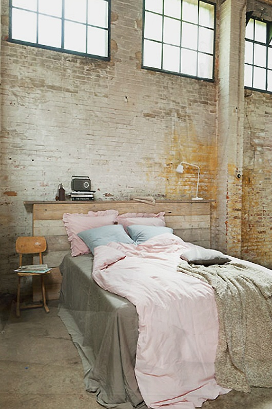 a shahby chic bedroom with a neutral brick wall, a reclaimed wooden bed and some vintage items