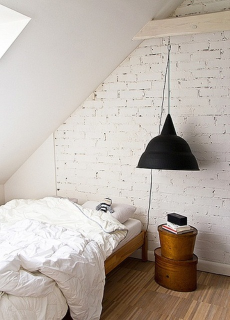 a Nordic guest bedroom with a fake white brick wall, a black lamp and wooden furniture