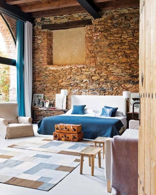 an eclectic bedroom with a stone wall, contemporary and vintage furniture and a glazed wall for more light and enjoying views