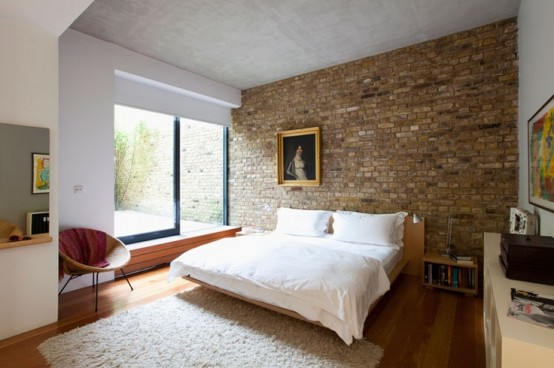 a neutral mid-century modern bedroom would have looked more boring and too polished without a brick wall in sandy tones