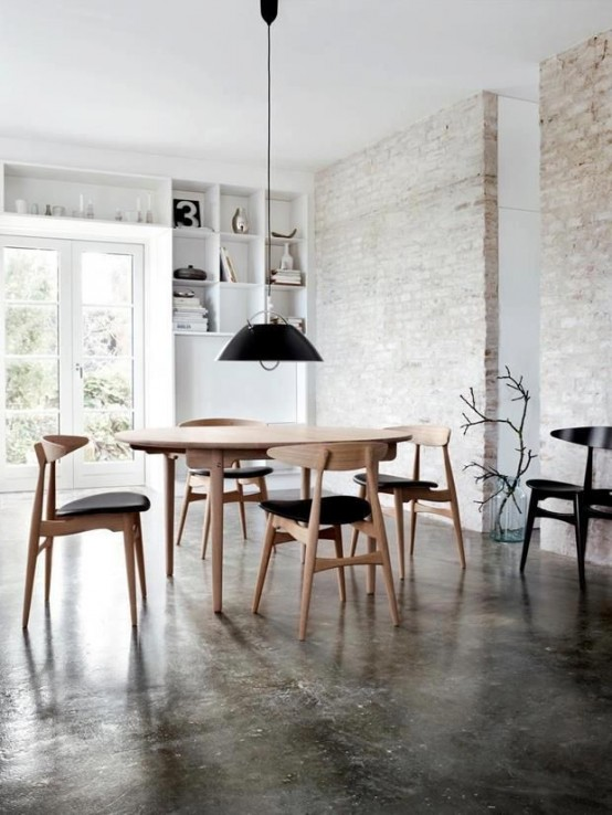 a Nordic dining room with whitewashed red brick walls, built-in shelves and a chic modern dining set with a black pendant lamp over it