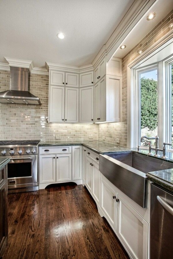 a vintage farmhouse kitchen with white cabinetry, a whitewashed red brick backsplash and stainless steel appliances
