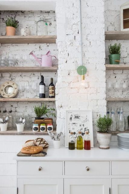 a contemporary Scandinavian kitchen with whitewashed brick walls, white cabinetry, open shelves, lamps and greenery is cool