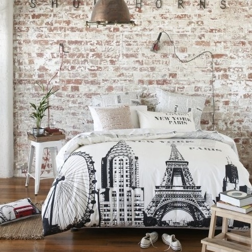 a modern bedroom with a shabby chic whitewashed brick wall, modern furniture and a pendant metal lamp, a woven rug