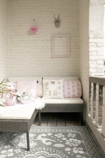 a balcony with whitewashed brick walls, a small sectional rattan sofa and printed pillows