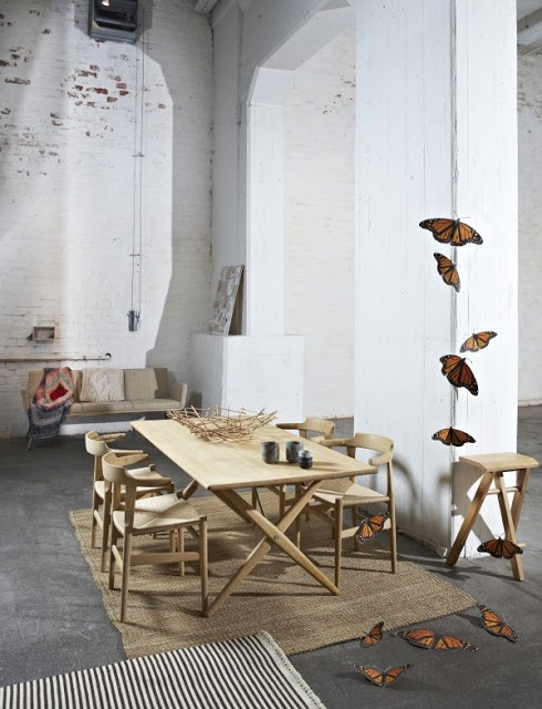 an eclectic space with whitewashed brick walls, double-height ceilings, modern wooden and leather furniture and butterflies for decor