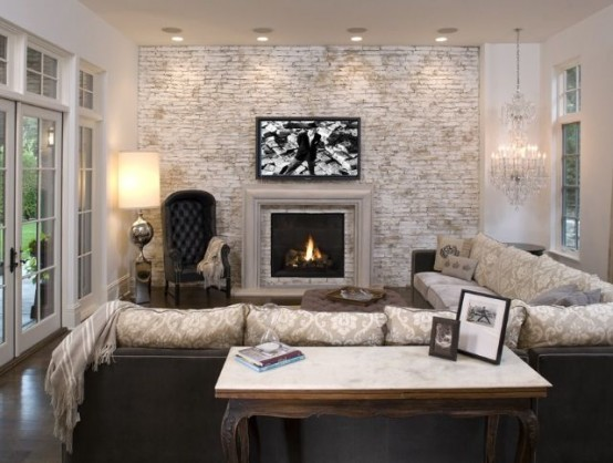 a vintage living room with a whitewashed brick wall, a fireplace, a crystal chandelier, a large corner sofa, a refined chair and lights