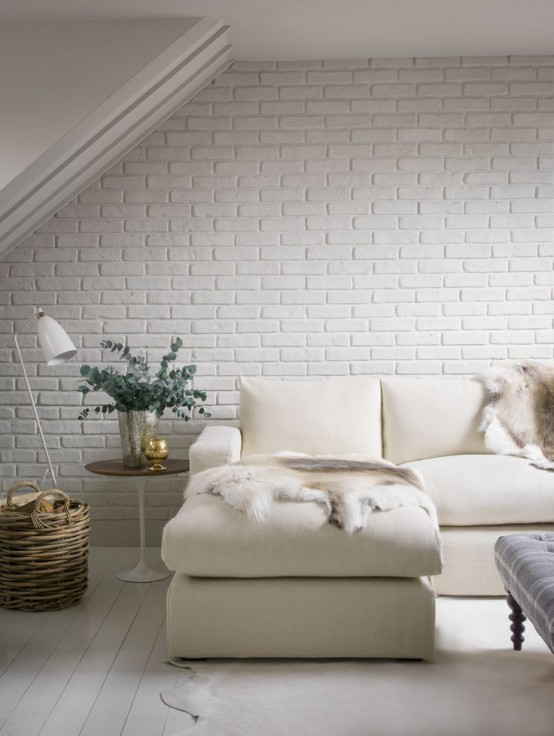 a modern neutral living room with a faux whitewashed brick wall, a corner sofa, a table and a baket is very welcoming