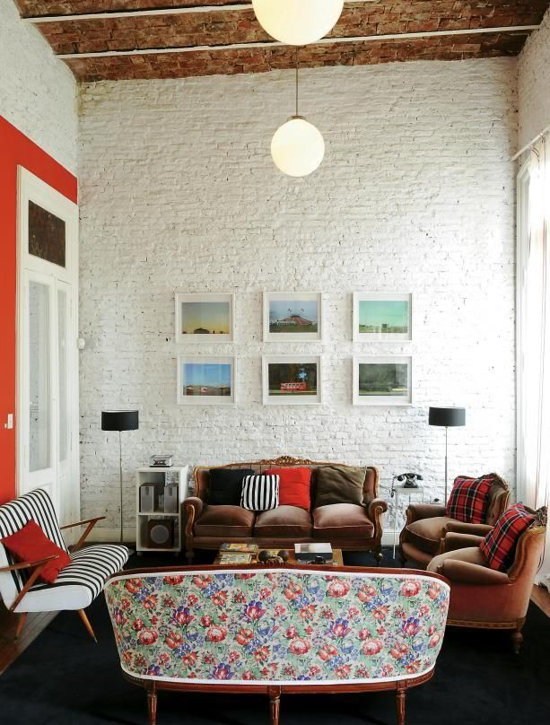 a mid century modern living room with whitewashed brick walls, elegant sofas and chairs, a chic gallery wall, bright and printed pillows and pendant lamps