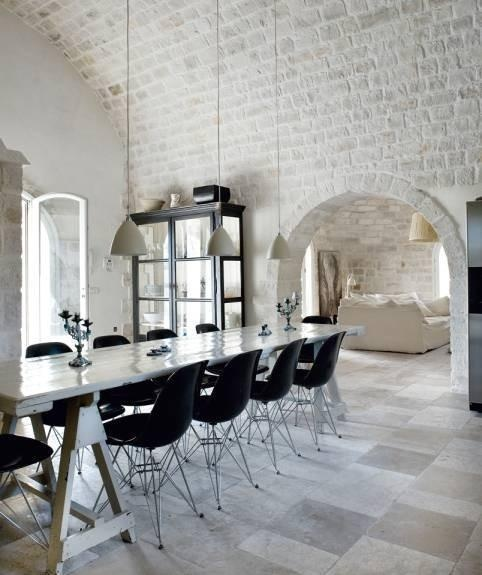 a beautiful dining space with whitewashed brick walls and a ceiling, a trestle table, black chairs and pendant lamps over the table