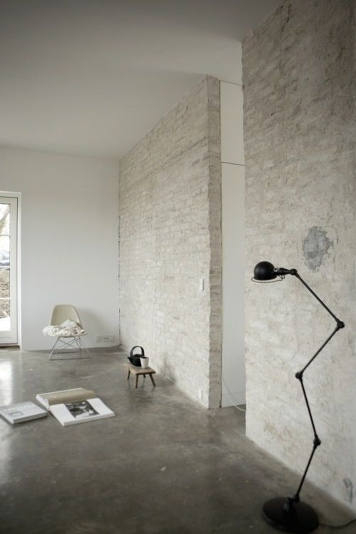 a Nordic space with whitewashed brick walls and a concrete floor, a black floor lamp and some furniture