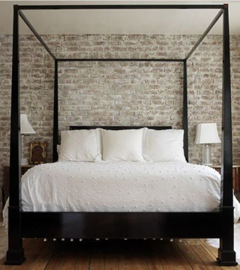 a vintage farmhouse bedroom with a whitewashed brick wall for an accent and more eye-catchiness and a dark heavy wooden bed