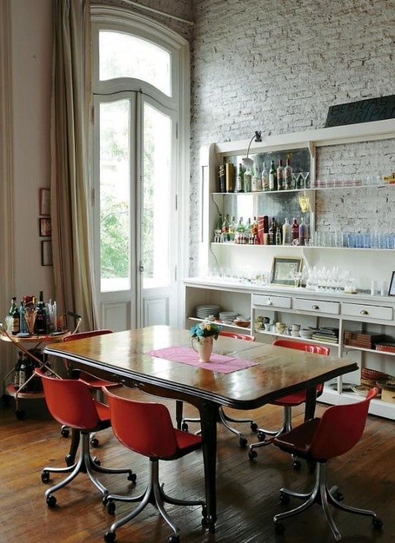 an eclectic dining space with a whitewashed bricl wall, a large buffet and shelves, a refined wooden table and modern red chairs