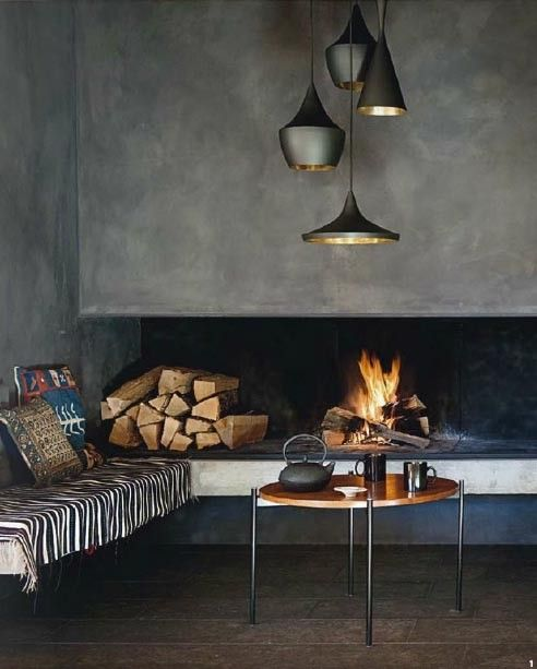 a stylish and cozy fireplace nook with an open minimalist fireplace, some firewood and a bench with pillows plus a cluster of pendant lamps