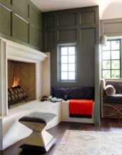 a stylish fireplace nook with an open fireplace, a small ccozy nook by the window with a pillow and a stool is welcoming and cozy