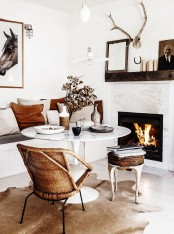 a small neutral nook with a stone clad fireplace, a matching round table, a banquette seating, a couple of stools for having meals here