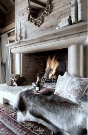 a cool space with an open fireplace clad with stone, with firewood, some animal skins and pillows and a bottle of champagne
