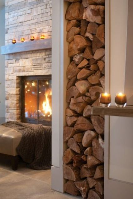 a welcoming space with a built-in fireplace clad with faux stone, a leather ottoman with a blanket and some candles around