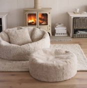 a modern neutral nook with a beige hearth, a coupel of large floor cushions and some books for curling here