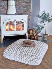 a white fireplace with firewood, potted plants, a crochet cushion is a lovely nook to spend time in