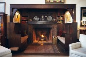 a dark and welcoming nook with a brick fireplace, a dark mantel with decor and tall benches with cushions and pillows