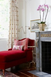 a fireplace nook with a refined and chic fireplace, a deep red lounger and a floor lamp plus a small round table between these two items for more elegance