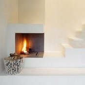 a minimalist nook with an open fireplace by the staircase and a metal basket for firewood plus a small nook to sit on the steps