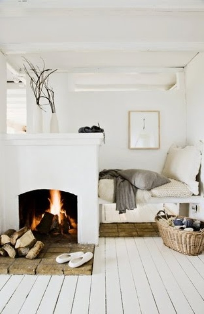 a Scandinavian nook with an open fireplace and firewood plus a small nook to sit in with cushions and pillows is welcoming
