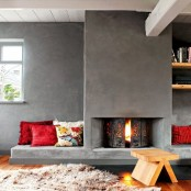 a contemporary space with a concrete clad fireplace and seating spaces with pillows plus a wooden stool for enjoying warmth here