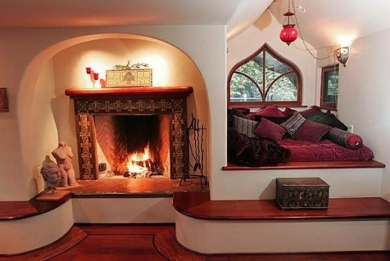a fireplace clad with tiles with a long step around it that might be used as a bench to enjoy warmth and coziness