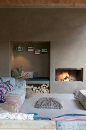 a minimalist fireplace nook with a built-in hearth and a built-in niche nook with books, a lamp and firewood under the bench is cozy