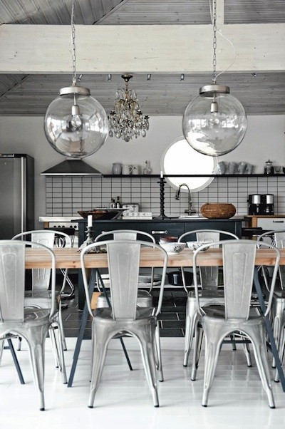 An amazing vintage metal chairs and glass orbs above them are things that make this kitchen special.
