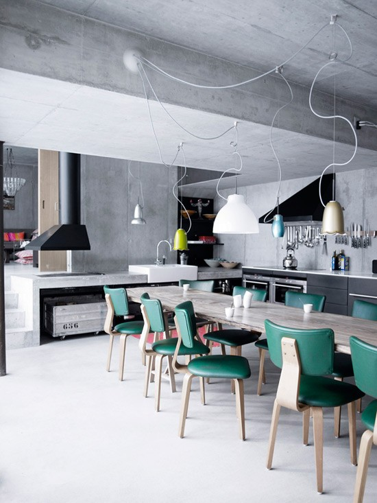 Bare concrete walls and ceilings is one of those things you can often find in industrial kitchens. On this kitchen creative light fixture and emerald chairs add a color splash concrete need.