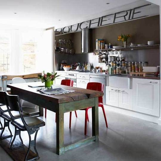Timeless white kitchen cabinets combined with red chairs and a weathered barn-like dining table make this kitchen look unbelievably good.